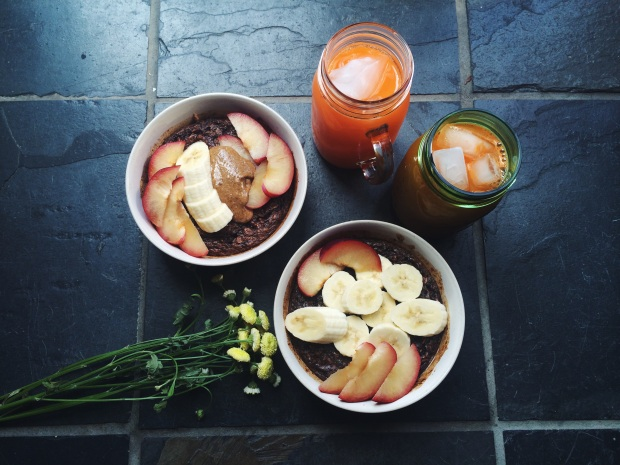 Baked cacao oatmeal topped with plums, banana and almond butter with carrot juice